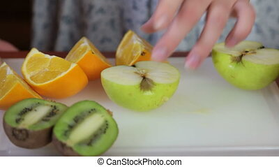 Fruits on chopping board - female hands sliced kiwi,...