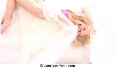 Beautiful blonde in white bed