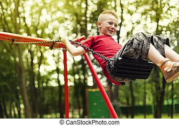 Cute boy swinging in a park
