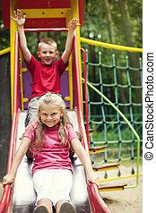 Two kids having fun on slide