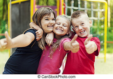 Happy children showing ok sign on playground