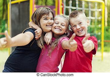 Happy children showing ok sign on playground