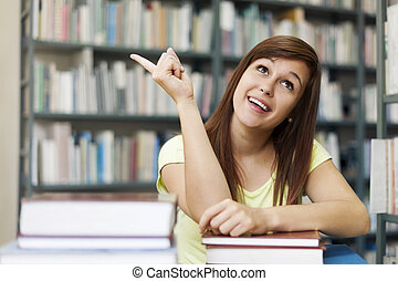 Beautiful student pointing at copy space