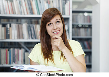Young woman daydreaming in library