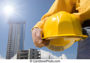 under construction - focus point on the hard-hat and hand,...