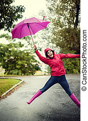 Cheerful woman jumping with umbrella