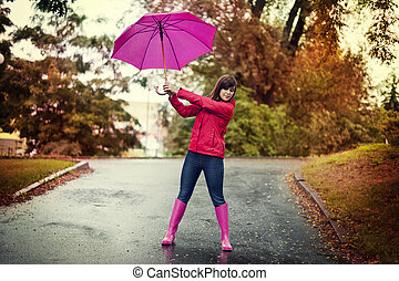 Young woman holding pink umbrella in a park