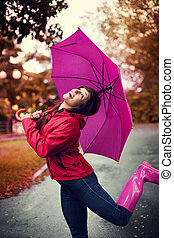 Cheerful woman with umbrella and rubber boots in the rain