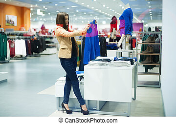 Attractive woman choosing clothes in shop