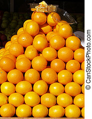 Pyramid of oranges in store front display - Oranges stacked...