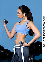 Athletic girl exercises with dumbbells