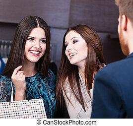 Talking about sales - Two girls speak with shop assistant...