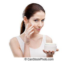 Woman putting on lifting cream from container on face -...