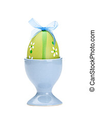 Green colored easter egg is in egg cup