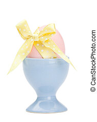 Colored easter egg with yellow ribbon in egg cup