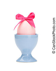 Colored easter egg with pink bow in egg cup