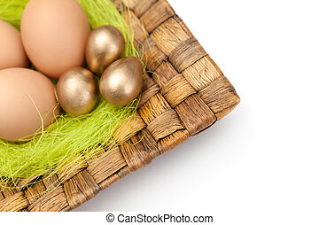 Brown and golden easter eggs are on wattled plate with sisal...