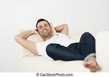 Happy male relaxing on couch at home