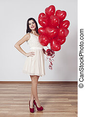 Woman holding many balloons in heart-shaped