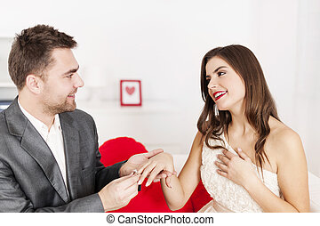Man putting a wedding ring on his girlfriends finger