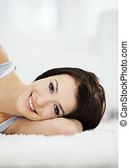 Attractive and smiling woman lying on the carpet
