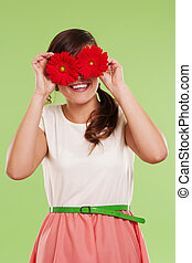 Smiling woman covering her eyes with two flowers