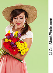Woman wearing straw hat holding spring flower