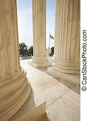 American flag viewed between pillars of Supreme Court...