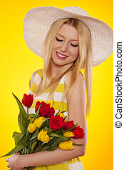 Spring portrait of a beautiful young woman with tulips