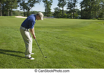 Golfer chipping onto green - Golfer preparing to chip onto a...
