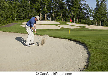 Golfer blasting out of bunker onto green - Golfer in a blue...