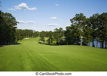 Golf fairway lined with trees near lake - Beautiful golf...