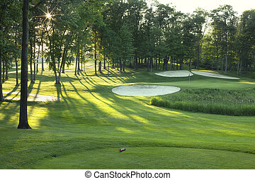 Golf green and tee box in late afternoon sunlight - Golf tee...