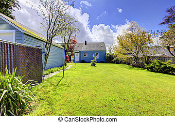 Backyard with small blue house and bright green spring grass.