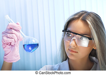 researcher - female researcher look at retort with blue...