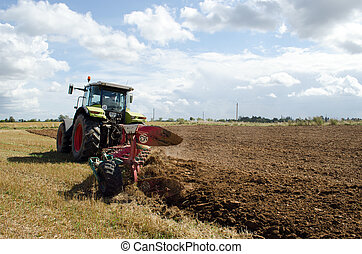 heavy agricultural machine tractor works in field