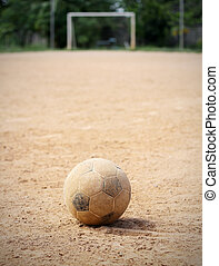 An old soccer ball on ground, goal is the background