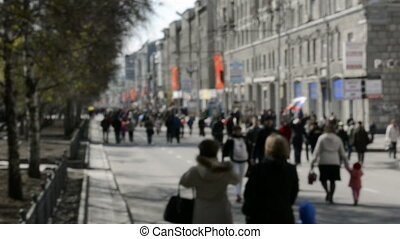 People are walking down the street during the festival of...
