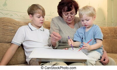 Granny with kids painting at home - grandmother with two...
