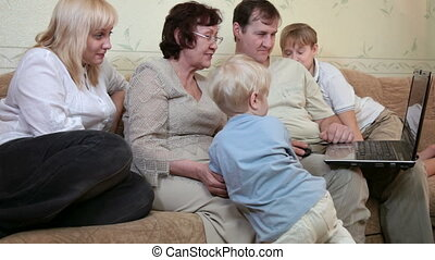 Family using laptop at home - Grandmother, parents and two...