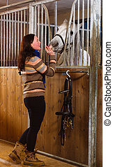Woman feeding horse in the stall, vertical format