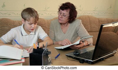 Home schooling - Tutor helping school boy to study at home