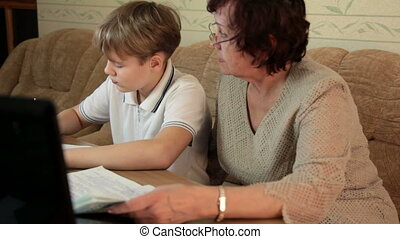 Doing Homework Together - Grandmother helping her grandson...
