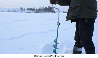 winter day on ice fisherman drilled - a cold winter day on...