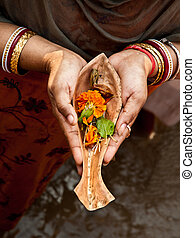 Prayer to the river goddess - Hands of a Hindu pilgrim...