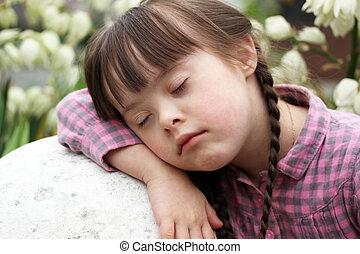 Portrait of beautiful young girl sleeping outside on flowers...