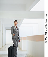 Smiling business woman with bag on wheels in business trip