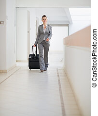 Business woman walking with bag on wheels
