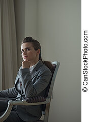 Thoughtful business woman sitting in chair in hotel room