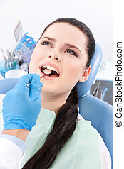 Dentist is looking for the defects in the oral cavity of the...